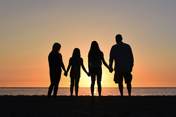 Group holding hands at sunset